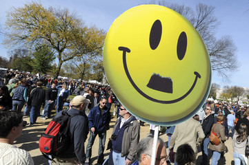 "A man holds a sign of a smiley face at the ""Rally to Restore Sanity and/or Fear"" on the National Mall in Washington"