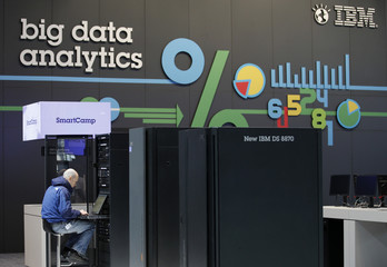 A technician works at a server in front of a big data analytics logo at the booth of IBM during preparations for the CeBIT trade fair in Hanover