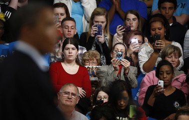 Members of the audience take pictures of U.S. President Obama as he participates in a campaign rally at Springfield High School in Ohio