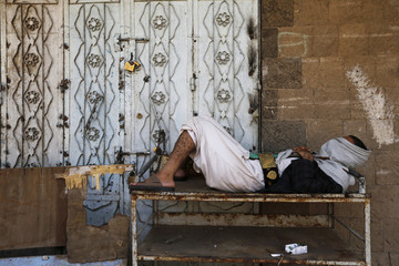 A follower of the Shi'ite Houthi movement sleeps on a table on the side of the main road leading to the airport in Sanaa