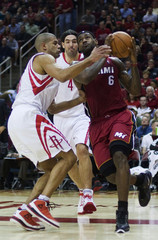 Miami Heat forward James is defended by Houston Rockets Battier and Scola as he goes in for a basket during their NBA game in Houston