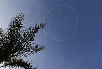 A smiley face is left in the skies by the DHL Extra 300 aerobatic plane during the Bahrain International Air Show