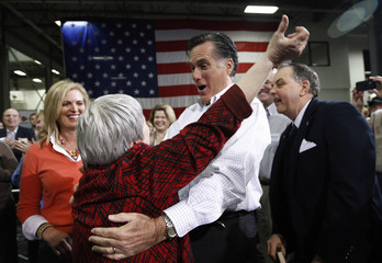 Romney is greeted by supporter Scotter at a town hall meeting at the Diamond V South Plant in Cedar Rapids, Iowa