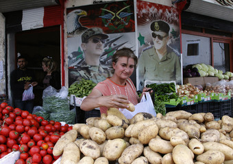A woman buys potatoes from a shop displaying pictures of Syria's President Bashar al-Assad and his father late President Hafez al-Assad, in al-Qardahah town, near Latakia city