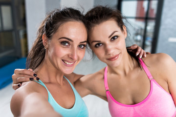 Two girls taking selfie wearing sports bra indoors. Close-up shot of female athletes smiling at camera hugging each other.