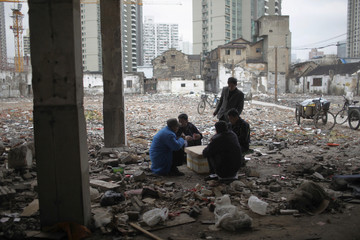 Migrant labourers play cards in an area where old residential buildings are being demolished to make room for new skyscrapers in downtown Shanghai