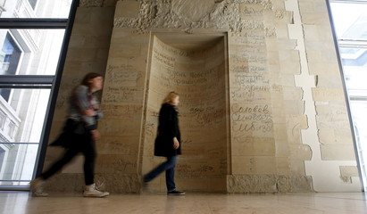 Visitors walk past original bits of graffiti with soldiers names and dates left behind from Russian Red Army soldiers in the last days of World War Two in 1945 on walls inside of the Reichstag building