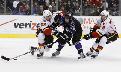Flames' Babchuk of Ukraine and Morrison attempt to stop Kings' Stoll during the second period of an NHL hockey game in Los Angeles
