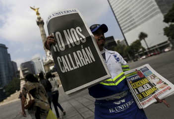 """A street vendor sells copies of Mexico's leading daily El Universal newspaper with a blackened-out front page that reads """"We will not be silenced"""", along a street in Mexico City"""