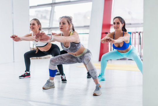 Young slim women in sportswear doing squat exercise during intensive circuit training in sporty