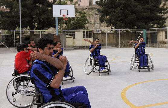 Disabled Afghans stretch on their wheelchairs on a basketball court in Kabul
