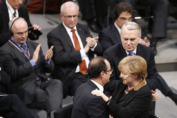 French President Hollande embraces German Chancellor Merkel after she spoke to joint assembly of German and French parliamentarians and officials at Reichstag in Berlin