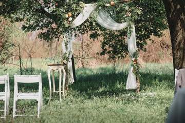 Wedding arch consist of withe, wooden constructions. Decorated by flowers and oranges. Rustic style