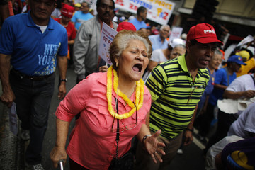 Elderly woman yells slogans during a march for peace in downtown Caracas