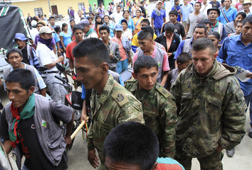 Indigeous residents escort Colombian soldiers to deliver them to the authorities in Caldono in the province of Cauca