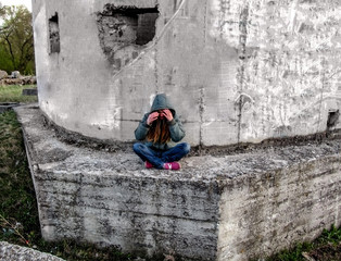 A girl in a hood sits in a lotus pose on a concrete wall. She has long blond hair and she hides her face with her hands