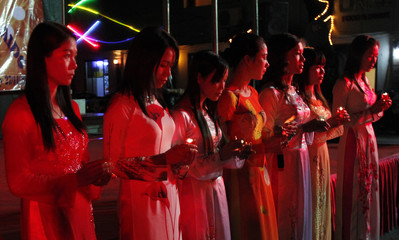 HIV-positive women carry lit candles during a HIV/Aids awareness campaign in Hanoi