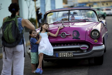 Young U.S. visitors pose for a photograph next to a vintage car in Havana