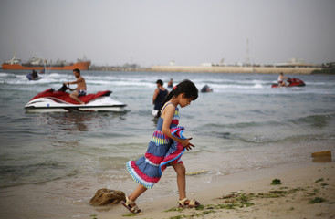 A Libyan girl plays at the beach in Tripoli