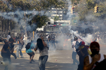 Anti-government protesters run away from tear gas launched by police during a protest in Caracas