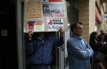 A man holds a placard as members of 36 families, who are living as squatters in an abandoned building, carry out a protest inside an Ibercaja bank branch in Seville