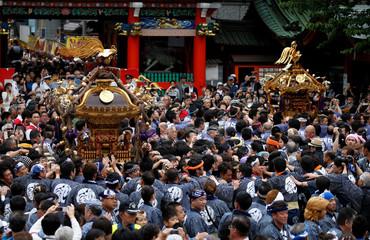 Shrine parishioners carry portable shrines into the Kanda Myojin Shrine during the Kanda festival, one of the three major Shinto festivals in Tokyo