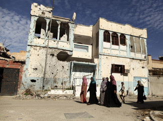 Libyan women walk past a house which was destroyed during fighting between pro and anti-Gaddafi fighters in Sirt