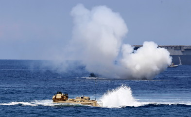 """U.S. military forces aboard Amphibious Assault Vehicles (AAV) manuevre on South China Sea near the shore of San Antonio, Zambales during the annual """"Balikatan"""" (shoulder-to-shoulder) war games with Filipino soldiers"""