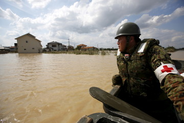 A Japanese Self-Defence Force's 1st Infantry Regiment soldier is seen on a boat conducting a search and rescue operation at a residential area flooded by the Kinugawa river, caused by Typhoon Etau at Araigi town in Joso