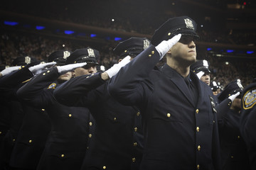 New York Police Department graduates salute as a solemn tribute to slain officers Ramos and Wenjian instead of throwing their gloves in the air in celebration in New York