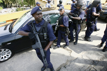 South African police protect President Jacob Zuma's vehicle as he leaves a meeting in Abidjan