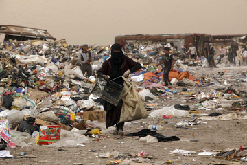 People collect garbage to be sorted and sold to nearby recycling centres in a district near Najaf