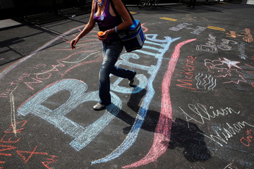 A woman walks across a chalk drawing of the Bernie Sanders campaign logo outside the Wells Fargo Center on the first day of the Democratic National Convention in Philadelphia