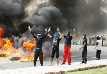 Anti-government protesters flash victory signs as they burn tyres in Budaiya