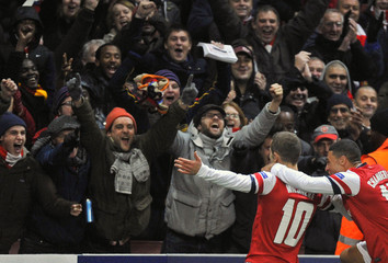Arsenal's Wilshere celebrates scoring against Montpellier with teammate Oxlade-Chamberlain during their Champions League Group B soccer match at the Emirates Stadium in London