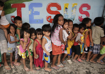 Residents living in a squatters area wait for a free meal consisting of rice, chicken and vegetables given on a daily basis by a South Korean Missionaries religious organization at a 3'0-clock Feeding Program building in a slum community of Tondo, Manila