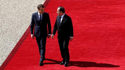 French President Emmanuel Macron escorts former President Francois Hollande who le