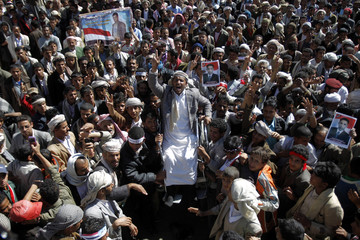 An anti-government protester on a wheelchair is carried by fellow protesters as he shouts slogans during a rally in Sanaa