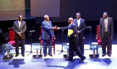 Uganda President Museveni and NRM party presidential candidate shakes hands with Mbabazi former prime minister and TDA presidential candidate during the presidential debate in Kampala