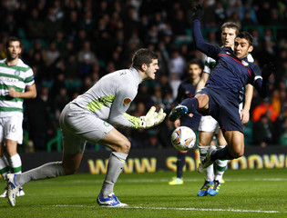 Atletico Madrid's Salvio challenges Celtic's goalkeeper Forster for the ball during their Europa League Group I soccer match at Celtic Park stadium in Glasgow
