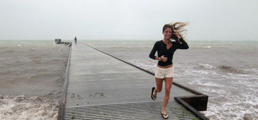 Unidentified woman leaves pier in high wind and rough surf as Tropical Storm Isaac moves over the island