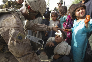 Chanrithy Ney, U.S. Navy Hospital Man attached with Weapons Company, 1st  Battalion, 3rd Marines treats an Afghan boy during patrol outside Camp Gorgak