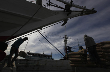Workers load sacks of cement onto a boat to be shipped to other provinces in Sunda Kelapa harbour in Jakarta