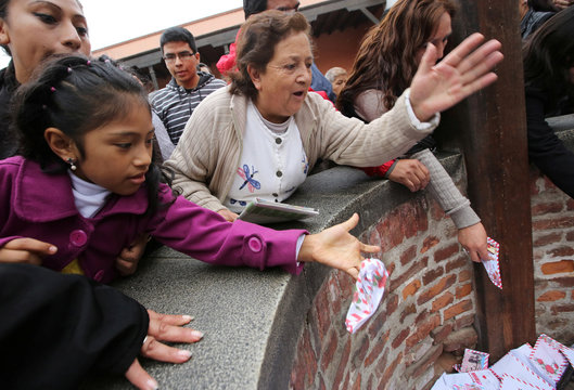 People throw letters into the well of wishes at Saint Rose's Church during celebrations of the anniversary of Santa Rosa de Lima (Saint Rose of Lima), patroness of Latin America and the Philippines, in Lima