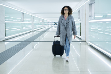 Black woman holding luggage ready to leave