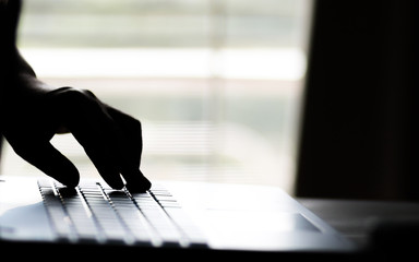 A hand reaching out through a laptop computer and signifying a cybercrime in internet theft while using online,