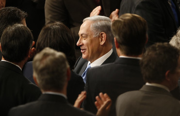 Israeli Prime Minister Netanyahu smiles as he is applauded by members of the U.S. Congress as he arrives to address a joint meeting of Congress in the House Chamber on Capitol Hill in Washington