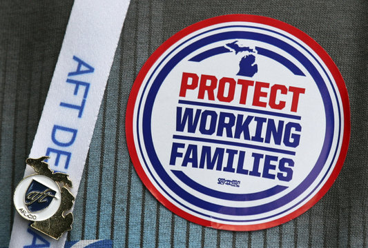 """American Federation of Teachers union member wears a """"Protect Working Families"""" sticker on his shirt during AFT convention in Detroit"""