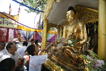 Devotee pours water on Buddha statue resting under a Bodhi tree during Kason Watering Festival celebrations in Yangon