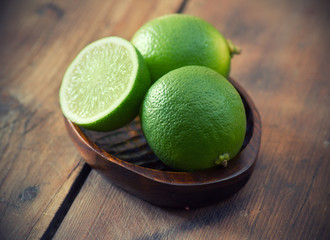 Fresh limes in wooden bowl